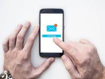 Les mains utilisant le smartphone avec l'email APP connectent sur l'écran photographie stock