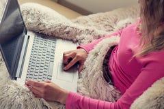 Les mains utilise son ordinateur portable femme se trouvant sur le lit avec l'ordinateur portable et l'achat photo stock