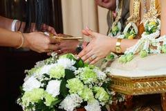 Les mains versant la bénédiction arrosent dans les mains de la jeune mariée Photographie stock