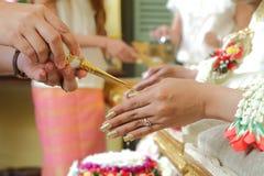 Les mains versant la bénédiction arrosent dans les mains de la jeune mariée du mariage thaïlandais Images libres de droits
