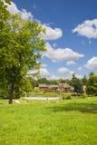Les maisons de Hamlet derrière l'étang Photographie stock libre de droits