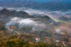 Les maisons de terres cultivables avec les nuages de tourbillonnement photographie stock