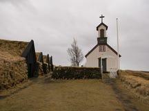 Les maisons de tourbe de Keldur avec la vieille église images stock