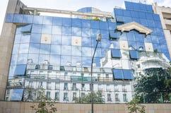 Les maisons historiques à Paris ont réfléchi sur le verre d'immeuble de bureaux moderne Photos stock