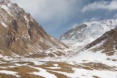 Les maisons minuscules parmi la neige ont couvert l'énorme gamme de montagne images libres de droits