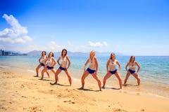 Les majorettes se tiennent dans des mains de pose de triangle sur des hanches sur le sable humide Images stock