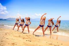 Les majorettes se tiennent dans des mains de triangle aériennes sur le sable humide Photo stock