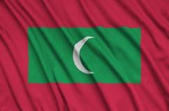 Les Maldives diminuent est dépeintes sur un tissu de tissu de sports avec beaucoup de plis Bannière d'équipe de sport photo stock