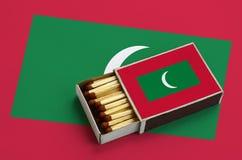 Les Maldives diminuent est montrées dans une boîte d'allumettes ouverte, qui est remplie de matchs et se trouve sur un grand drap images stock
