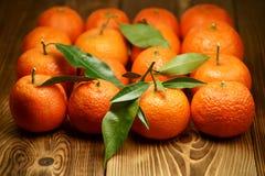 Les mandarines avec les feuilles vertes ont arrangé dans une place sur les conseils en bois images libres de droits