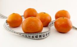 Les mandarines et la bande de centimètre sur un fond blanc portent des fruits image stock