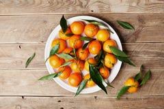 Les mandarines ou les mandarines avec les feuilles vertes sur la table en bois rustique de ci-dessus dans l'appartement étendent  Images libres de droits