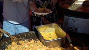 Les marchands ambulants préparent le riz asiatique traditionnel avec des légumes sur la rue banque de vidéos
