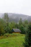 Les matins refroidissent la maison dans le brouillard et la vapeur de forêt Photographie stock libre de droits