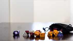 Les matrices colorées de roleplaying ont dispersé sur une table avec la réflexion Photographie stock libre de droits