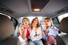 Les meilleures amies à la mode entrent dans la voiture, apprécient la vie, heure d'été, le temps de achat, période du repos avec  Image libre de droits