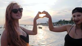 Les meilleures amies font des mains de coeur sur la mer de fond, la jeune femme deux posant pour la photo au coucher du soleil, banque de vidéos
