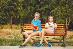 Les meilleures amies lisent le journal intime se reposant sur le banc Image stock