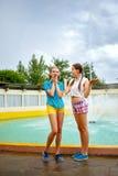 Les meilleures amies parlant en parc près de la fontaine Image stock