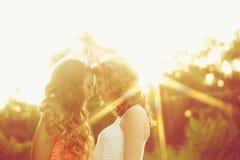 Les meilleures amies regardent dans chaque autres observe Coucher du soleil Photographie stock