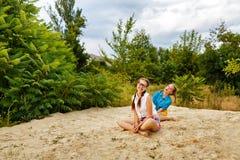Les meilleures amies s'asseyant sur le sable à la plage Photo stock