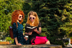 Les meilleures amies sont livre de lecture en parc Images stock
