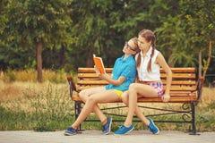 Les meilleures amies sont livre de lecture tout en se reposant sur le banc Photographie stock