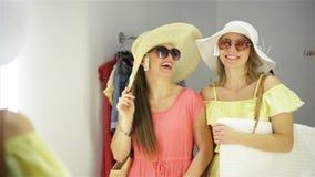 Les meilleurs amis dansent dans la cabine d'essayage dans le centre commercial Deux jolies filles ont beaucoup d'amusement passan banque de vidéos