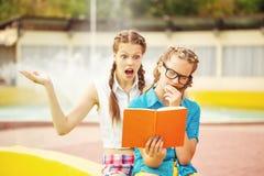 Les meilleurs amis discutent le livre dans le parc Photo libre de droits