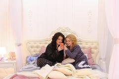 Les meilleurs amis féminins observent des actualités sur l'Internet sur le smartphone et le cha images stock