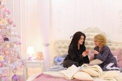 Les meilleurs amis féminins observent des actualités sur l'Internet sur le smartphone et le cha Photo libre de droits