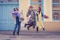 Les meilleurs amis ont satisfait sauter sur la rue après l'achat Photo stock