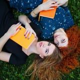 Les meilleurs amis sont des étudiants ensemble sur la pelouse Images stock