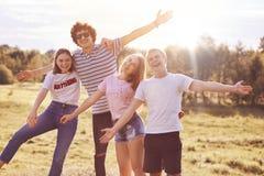 Les meilleurs camarades joyeux célèbrent quelque chose extérieure, ont le pique-nique, étirent des mains heureusement, donnent l' Photographie stock