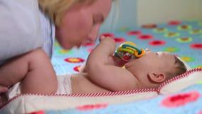 Les meilleurs moments de la vie, une jeune m?re heureuse affectueuse ?treint un fils soignant, sur une couverture bleue avec des  banque de vidéos