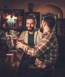 Les meilleurs riends buvant de la bière pression au compteur de barre dans le bar Image libre de droits