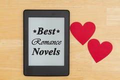 Les meilleurs romans Romance textotent sur un e-lecteur sur un bureau en bois avec deux coeurs image libre de droits