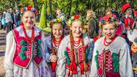 Les membres de filles de la danse folklorique polonaise GAIK marchant en parc Photo stock