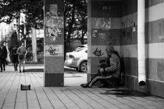 Les mendiants affamés sans abri de musicien avec l'accordéon demande l'aumône sur la rue près du mur photo stock