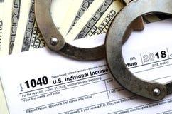 Les menottes de police se trouvent sur la feuille d'impôt 1040 Le concept de proble photographie stock