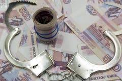 Les menottes sont sur les billets de banque russes image stock