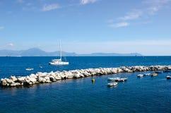 Les mensonges d'un yacht de catamaran de navigation ont amarré juste en dehors d'un briseur de vague en pierre dans la baie de Na image stock