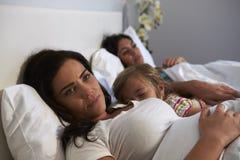 Les mensonges de femme se réveillent tandis que sa fille et associé féminin dorment Photos stock