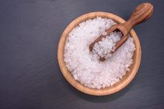 Les mensonges de sel dans une tasse en bois dans elle se trouve un scoop en bois au centre d'un conseil en pierre noir Photographie stock