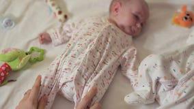 Les mensonges nouveau-nés sur le sien dos et sa mère masse ses jambes Physiothérapie pour des nouveaux-nés banque de vidéos