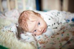 Les mensonges nouveau-nés sur son estomac et apprennent à garder votre tête images stock