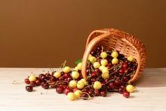 Les merises rouges et blanches ont débordé un panier tissé Photographie stock libre de droits