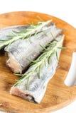 Les merluches crues fraîches pêchent avec des branches de romarin sur le conseil en bois rond Image stock