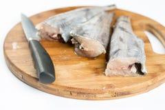 Les merluches crues fraîches pêchent sur le conseil cuting en bois avec le couteau Image stock