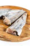 Les merluches fraîches pêchent sur le conseil en bois prêt pour la copie commerciale pour le marché Photographie stock
